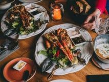 Langoustines su insalata con le salse in ristorante immagine stock
