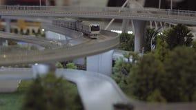 Langs de spoorwegbrug, een broodplankmodel op een schaal zal reizen De lay-out van het grondstation, close-up stock video