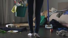 Langs met afschuw vervulde de vrouw knoeit links na partij in haar flat, die de dienst schoonmaken stock videobeelden