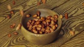 LANGSAM: Abgezogene Erdnüsse fallen in einen hölzernen Teller auf einer Tabelle stock footage