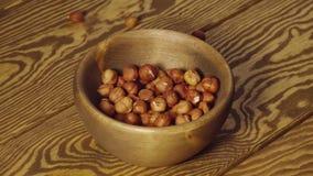 Langsam: abgezogene Nüsse fallen in einen hölzernen Teller auf einer Tabelle stock video