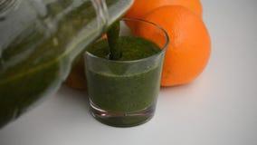 Langsam strömender grüner Smoothie in Glas stock footage