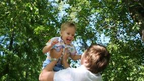 Langsame Bewegung ein junger Vater, der sein lachendes Baby in der Luft wirft Im Freienerholung stock video