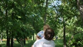 Langsame Bewegung ein junger Vater, der sein lachendes Baby in der Luft wirft Im Freienerholung stock video footage