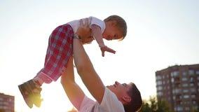 Langsame Bewegung ein junger Vater, der sein lachendes Baby in der Luft wirft Im Freienerholung stock footage