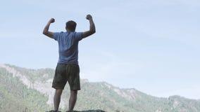 Langsame Bewegung Ein Mann hebt aktiv seine Hände oben an und genießt zu klettern stock footage