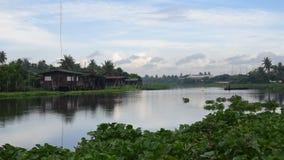 Langschwänziges Boot in Fluss Tha Chin mit Haus neben Fluss stock footage