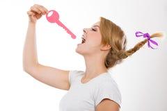 Teenage girl with braid biting key. Language barrier concept. Teenage blonde girl with braid hair biting big pink key royalty free stock photography