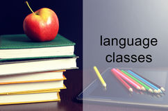 Language classes apple book stack. Educational concept in the photos as a pile of books and a fresh apple as a source of vitamins for study Royalty Free Stock Photography