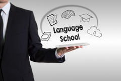 Language School concept with young man holding a tablet computer Royalty Free Stock Image