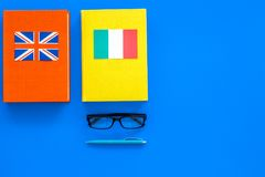 Language study concept. Textbooks or dictionaries of foreign language near flags on blue backgrond top view copy space. Language study concept. Textbooks or Stock Photo
