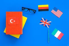 Language study concept. Textbooks or dictionaries of foreign language near flags on blue backgrond top view copy space. Language study concept. Textbooks or Stock Image