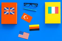 Language study concept. Textbooks or dictionaries of foreign language near flags on blue backgrond top view copy space. Language study concept. Textbooks or Stock Images