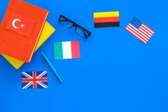 Language study concept. Textbooks or dictionaries of foreign language near flags on blue backgrond top view copy space. Language study concept. Textbooks or Royalty Free Stock Images