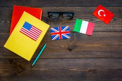 Language study concept. Textbooks or dictionaries of foreign language near flags on dark wooden backgrond top view copy. Language study concept. Textbooks or Stock Photo