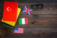 Language study concept. Textbooks or dictionaries of foreign language near flags on dark wooden backgrond top view copy. Language study concept. Textbooks or Royalty Free Stock Photography
