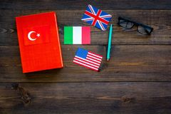 Language study concept. Textbooks or dictionaries of foreign language near flags on dark wooden backgrond top view copy. Language study concept. Textbooks or Royalty Free Stock Image