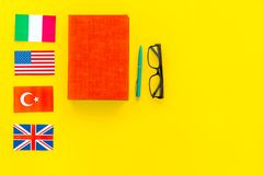 Language study concept. Textbooks or dictionaries of foreign language near flags on yellow backgrond top view copy space. Language study concept. Textbooks or Royalty Free Stock Image