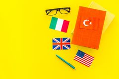 Language study concept. Textbooks or dictionaries of foreign language near flags on yellow backgrond top view copy space. Language study concept. Textbooks or Stock Photos