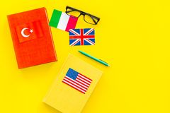 Language study concept. Textbooks or dictionaries of foreign language near flags on yellow backgrond top view copy space. Language study concept. Textbooks or Stock Image