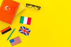 Language study concept. Textbooks or dictionaries of foreign language near flags on yellow backgrond top view copy space stock photography