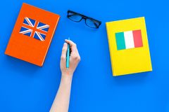 Language study concept. Textbooks or dictionaries of foreign language near italian and great britain flags on blue. Backgrond top view Royalty Free Stock Image