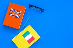Language study concept. Textbooks or dictionaries of foreign language near italian and great britain flags on blue. Backgrond top view Stock Photography