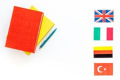 Language study concept. Textbooks or dictionaries of foreign language near flags on white backgrond top view copy space. Language study concept. Textbooks or Stock Image