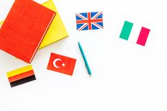 Language study concept. Textbooks or dictionaries of foreign language near flags on white backgrond top view copy space. Language study concept. Textbooks or Royalty Free Stock Photo