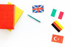 Language study concept. Textbooks or dictionaries of foreign language near flags on white backgrond top view copy space. Language study concept. Textbooks or Royalty Free Stock Image