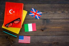 Language study concept. Textbooks or dictionaries of foreign language near flags on dark wooden backgrond top view copy. Language study concept. Textbooks or Royalty Free Stock Photos