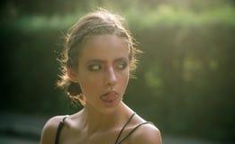 Langue d'exposition de jeune femme sur le visage de maquillage, beauté photographie stock libre de droits