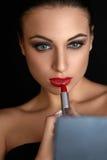 Languettes rouges Femme de Beutifull faisant le maquillage appliquant le rouge à lèvres Photo libre de droits