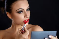 Languettes rouges Femme de Beutifull faisant le maquillage appliquant le rouge à lèvres Images stock