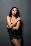Languid brunette posing in black silk negligee Royalty Free Stock Image