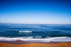 Languid ocean. A view from the shore of the beach to the horizon featuring a calm ocean Stock Image