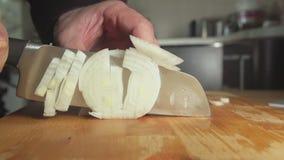 Langzaam-CLOSE-UP: De kok snijdt een uibol op een raad stock footage