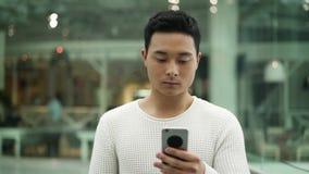 Langzaam die motiemidden van Aziatisch mannetje wordt geschoten die met een telefoon op venstersachtergrond lopen stock video