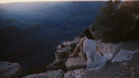 Langzaam motie cinematic schot van opgewekte jonge vrouw met haar die in de windzitting bij epische zonsondergang Grand Canyon bl stock video