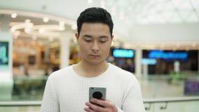 Langzaam motie middenschot van Aziatisch mannetje die met een telefoon op vage achtergrond lopen stock footage