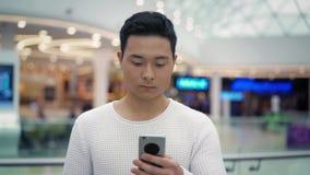 Langzaam motie middenschot van Aziatisch mannetje die met een telefoon op vage achtergrond lopen stock videobeelden