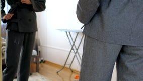 Langzaam motie slank meisje in elegant grijs bureaukostuum bij spiegel stock video