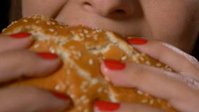 Langzaam motieclose-up van hongerige jonge vrouw die de sandwichhamburger eten van het troep ongezonde snelle voedsel stock video
