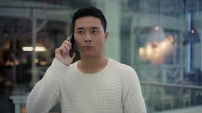 Langzaam motiemidden dat van Aziatisch mannetje wordt geschoten die op telefoon spreken terwijl het lopen stock video