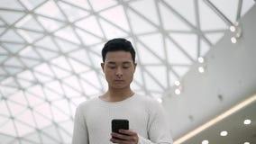 Langzaam motiemidden dat van Aziatisch mannetje wordt geschoten dat met een telefoon op plafondachtergrond loopt stock videobeelden