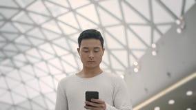 Langzaam motiemidden dat van Aziatisch mannetje wordt geschoten dat met een telefoon op plafondachtergrond loopt stock video