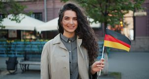 Langzaam motieportret dat van Duitse patriot zich in openlucht met vlag van Duitsland bevindt stock footage