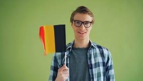 Langzaam motieportret die van vrolijke persoon Duitse vlag en het glimlachen houden stock video