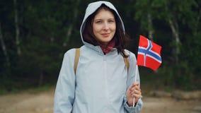 Langzaam motieportret van aantrekkelijke Noorse sportenventilator die officiële zich in bos bevinden en vlag die van Noorwegen go stock video