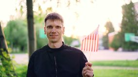Langzaam motieportret van de Amerikaanse mens die nationale vlag van de V.S. golven, en camera glimlachen bekijken Gelukkige jong stock video
